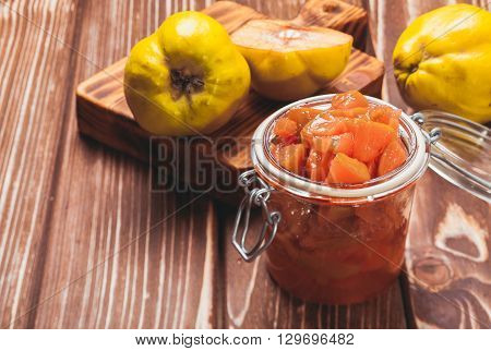 Quince jam in the glass jar and fruits on the background