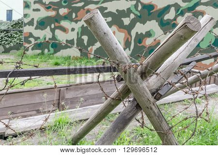 Wooden antipersonnel obstacle with barbed wire.Small depth of field