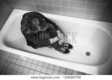 Stressed Sad Teenage Girl Sitting In Empty Bath