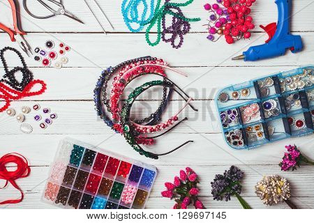 Plastic berries, flowers, beads and instruments for doing handmade headbands. Top view