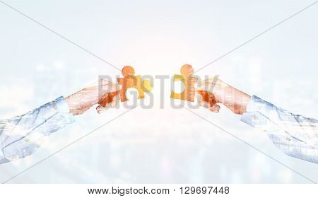 Businessmen putting two puzzle pieces together on city background. Double exposure