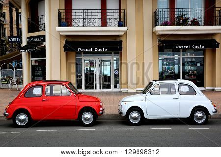 Menton France - May 14 2016: Two small Italian cars Fiat 500 Parked in a Parking Lot in Menton. The red car is a Fiat 500 R and the white is a Fiat 500 F