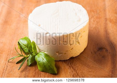 Salted soft cheese with basil leaf on the board