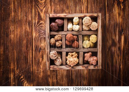 Assorted Chocolate candies in wooden box sells. Luxury handmade sweets