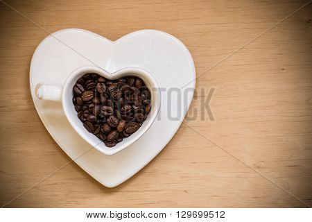 Heart shaped white plate and cup filled with roasted coffee beans on wooden table background. Top view