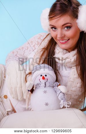 Smiling pretty cute woman holding little snowman. Attractive girl in earmuffs and white sweater pullover in studio on blue. Winter fashion.
