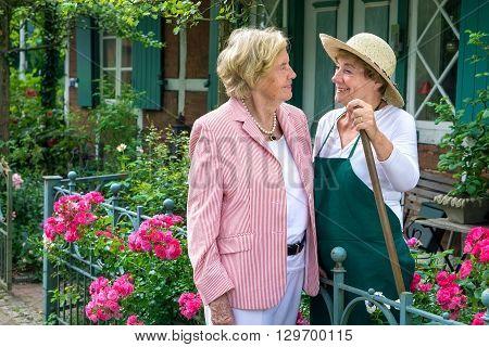 Two Senior Women Talking Together In Garden
