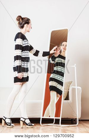Fashion and shopping. Woman trying dress sweater choosing clothing. Attractive female shopper looking in mirror standing in clothes store.