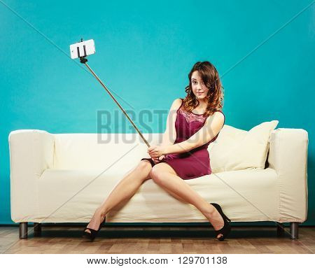 Technology internet and happiness concept. Young woman funny girl taking self picture selfie with smartphone camera on stick while sitting on sofa at home