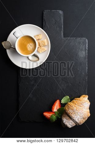 Espresso coffee cup and croissant with fresh strawberries on black  slate stone board over dark background. Top view, copy space
