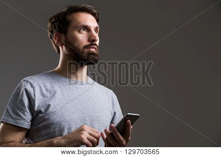 Bearded man with smartphone in hand looking up on dark grey background