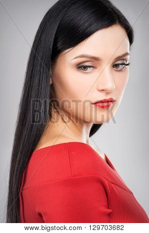 Side potrait of attractive brunette girl in red clothing looking down