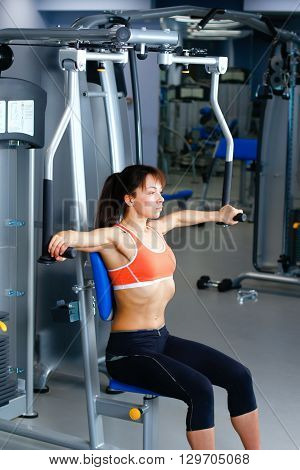 Sports young woman doing exercises on trainer back machine in the gym.