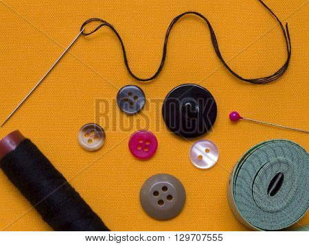 Thread needle, bobbin, sewing tape measure and buttons.