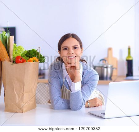 Portrait of a smiling woman cooking in her kitchen sitting.