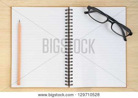 Top view of open spiral notebook pencil and black glasses on wood table