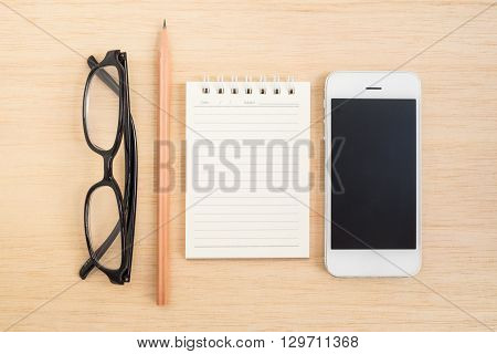 Top view of black glasses pencil notebook and mobile phone lay on wooden background