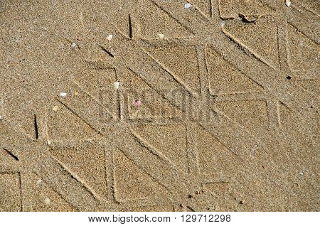 Pattern on beach sand made by a vehicle tyre