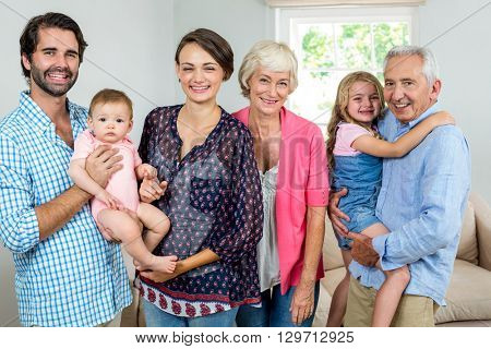 Portrait of cheerful multi-generation family in living room