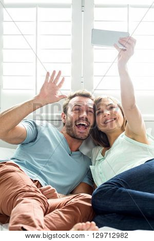 Cheerful couple taking selfie while relaxing on bed at home