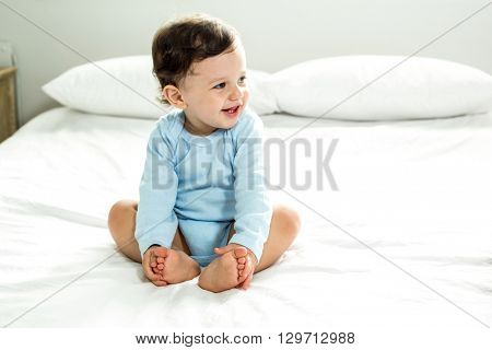 Full length of baby boy smiling while sitting on bed at home