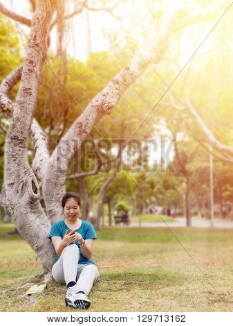 One women happiness relax enjoy with smart phone at the garden under sunlight with warm / soft color tone