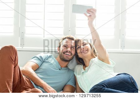 Happy couple taking selfie while relaxing on bed at home