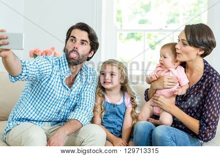 Family making faces while taking selfie on sofa at home