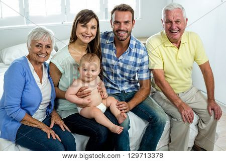 Portrait of happy multi-generation family sitting on bed at home