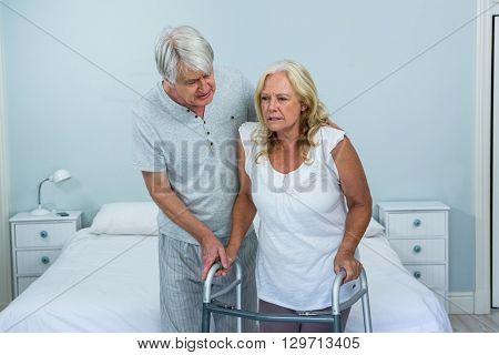 Senior man helping woman to walk in bedroom at home