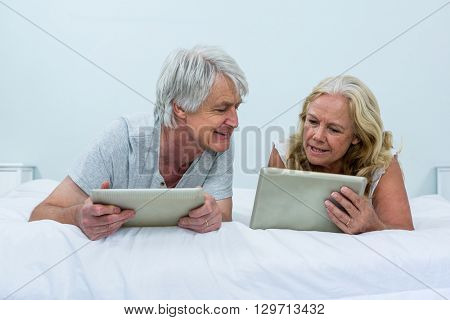 Senior couple talking while using digital tablets in bedroom at home