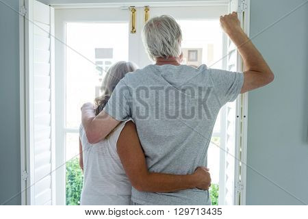 Rear view of senior couple with arms around looking through window at home