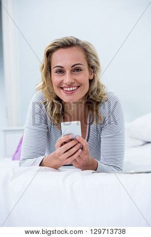 Portrait of young woman with mobile phone lying on bed in room