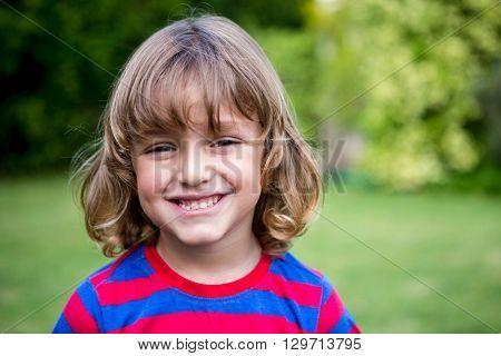 Portrait of cute smiling boy in back yard