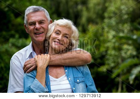 Portrait of senior man embracing wife from behind in back yard