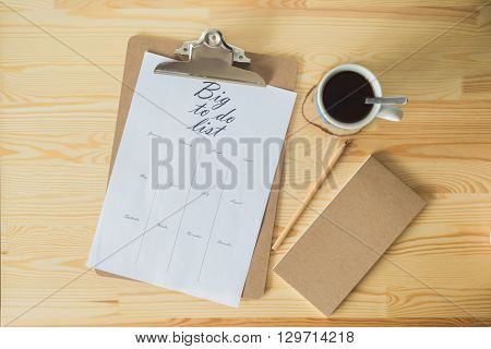 To do list with a cup of coffee on wooden