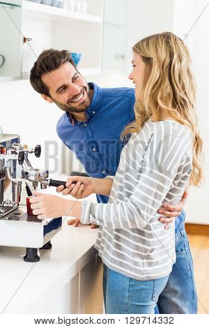 Young couple preparing coffee from coffeemaker at home