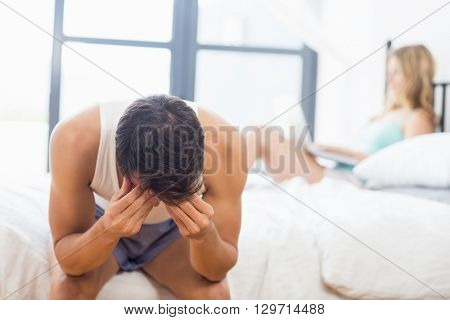 Tensed young man sitting on bed in bedroom