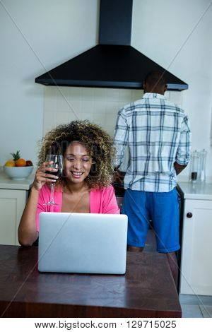 Woman using laptop and having wine while man cooking food in background at kitchen