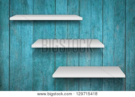 Three white shelves on blue wooden texture background, stock photo