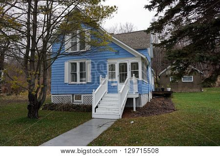 HARBOR SPRINGS, MICHIGAN / UNITED STATES - DECEMBER 23, 2015: A blue home under the bluff on Fourth Street in Harbor Springs.