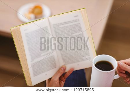 Midsection of woman reading book while holding coffee cup at home