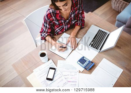 High angle view of woman writing in notepad with laptop at table