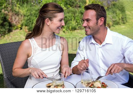 Smiling young couple having meal while sitting on chairs at park