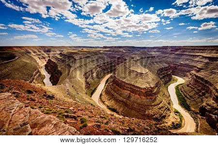 Goosenecks state Park Utah. Shows the San Juan River and clouds in the blue sky.