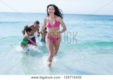Woman running against family standing on sea shore at beach