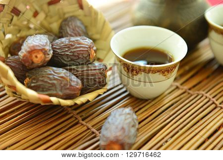 Ripped dates in a natural bowl with black coffee - close up
