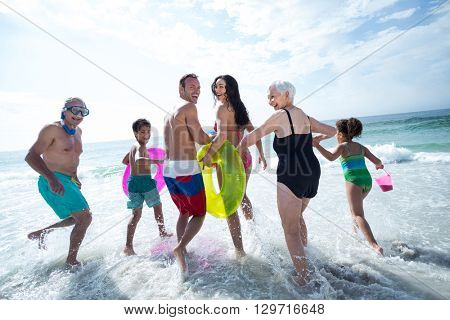 Multi- generation family laughing while running on sea shore at beach