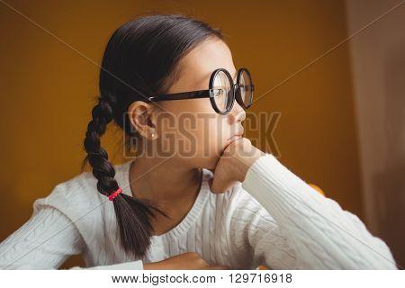 Schoolchild touching her chin at school