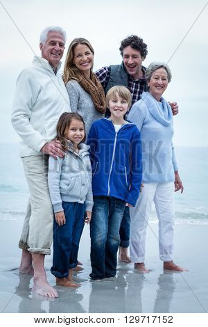 Portrait of happy family standing at beach against sky